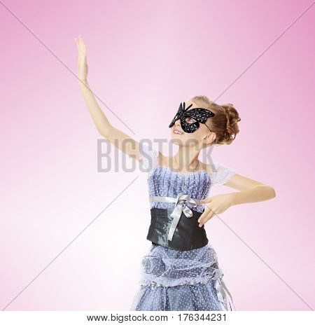 Slender little girl , with beautiful hair on his head, elegant long Princess dress.Posing in carnival mask.She looks at his palm as a mirror.Pale pink gradient background.
