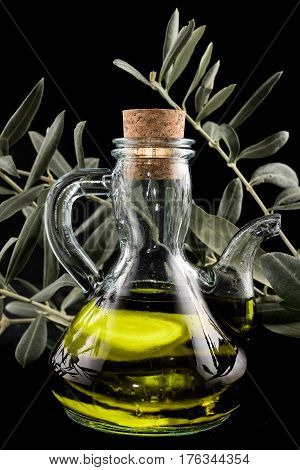 A bottle of extra virgin oil with an olive branch as a background