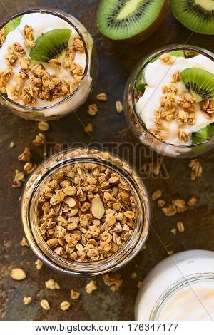 Crunchy almond and oatmeal granola in jar with yogurt kiwi granola parfait in glasses on the side photographed overhead on slate with natural light (Selective Focus Focus on the top of the granola and the parfaits)