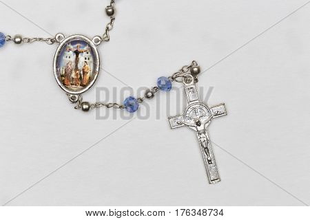 A rosary with a crucifix on withe background