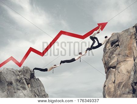 Businessmen working together to form a bridge between two mountains and raising an arrow