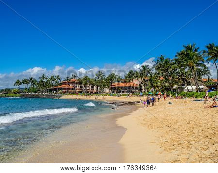 KAUAI, USA - MAR 3: Tourists and locals enjoy Poipu Beach on March 3, 2017 on Kauai, Hawaii. Poipu Beach is one of the most popular tourist areas on the island of Kauai and has many excellent hotels.