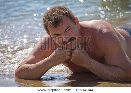 The Man Sunbathes On Sand