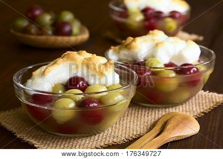 Stewed red and green gooseberry dessert with meringue in glass bowls photographed with natural light (Selective Focus Focus on the front of the meringue in the first bowl)