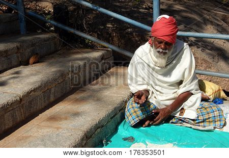 KEESRAGUTTA,HYDERABAD,INDIA-FEBRUARY 24:Indian Hindu senior man seeks help or alms or begs on stairs of temple during Mahasivaratri festival on Frbruary 24,2017 in keesaragutta,Hyderabad,India.
