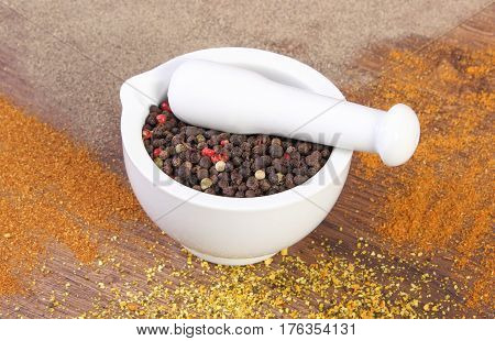 Colorful Pepper In Mortar And Powdery Pepper On Rustic Boards