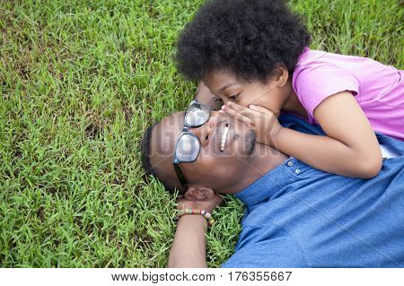 African American father and little kid whispering and gossiping with trust on green grass - with copyspace