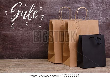 Mockup of blank shopping bags. Sale discounts. Brown and black craft packages. Concept for sales or discounts. Recycled paper. Wooden rustic board.