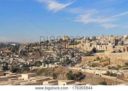 Dormition Abby, St. Peter in Gallicantu and al-Aqsa Mosque in a panoramic view of Jerusalem from a cemetery on the Mount of Olives in Israel beside the Kidron Valley.