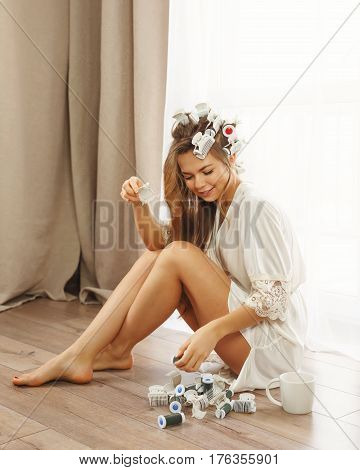 Cute Young housewife sitting on the floor near the window. Girl in a bathrobe and curlers hair done. Good morning.