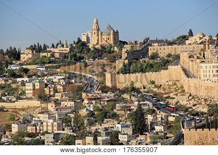 Dormition Abby and Old City Walls in a panoramic view of Jerusalem from the Mount of Olives in Israel beside the Kidron Valley.