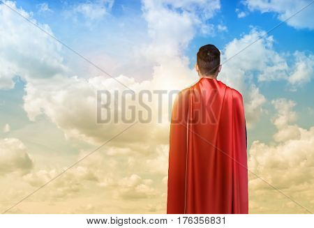 A businessman in super hero cape standing turned back on the sky background. Business hero. Confidence and success. New opportunities.