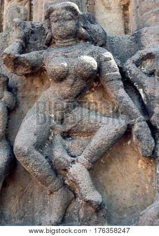 Stone carving ruins of an woman traditional dancer at an ancient Hindu Temple