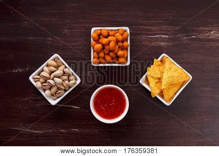 Nachos chips. Tortilla snacks with sweet salsa or chilli sauce. Mexican salsa and pistachios nuts. On rustic wooden background.