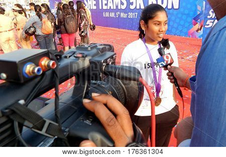 HYDERABAD,INDIA-MARCH 5:TV reporter interview 5 Km runner in She team celebration protection of women and child on International women day activity on March 5,2017 in Hyderabad,India.