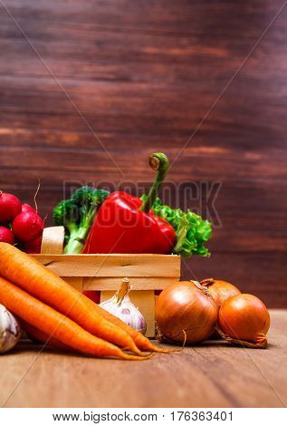 Vegetables. Onion, carrot and red pepper. Lettuce salad, garlic and brocoli. Onion and radish. Wooden basket on rustic table.