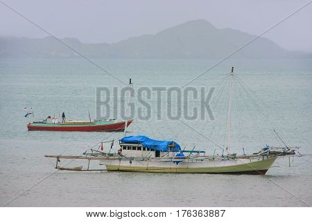 Traditional outrigger boat anchored at Labuan Bajo town on Flores Island Nusa Tenggara Indonesia. The local economy in the town is centered around the ferry port and tourism.