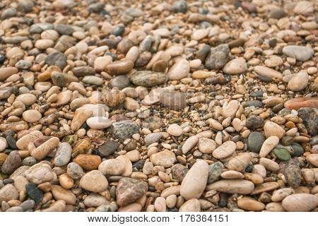 Texture of dry round colored sea pebbles on pebble beach, close-up. Pebbles stone background.  Small stones gravel texture, background from colored round stone.