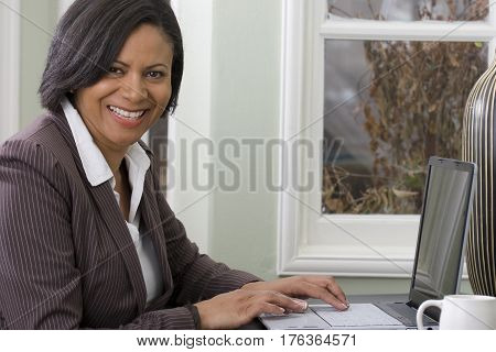 Confient African American woman working from home.