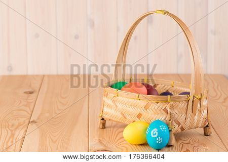 Laconic Easter Composition - Basket With Colored Eggs On Wooden Boards