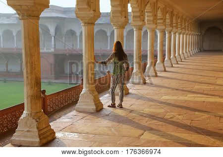 Young woman standing in colonnade walkway leading to Diwan-i- Khas in Agra Fort Uttar Pradesh India. The fort was built primarily as a military structure but was later upgraded to a palace.