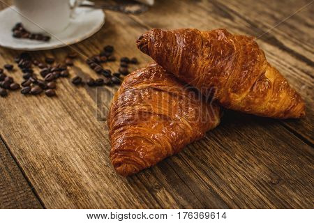 Traditional french breakfast croissant and coffee on wood table