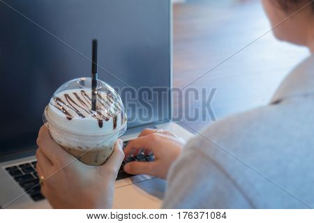 Woman typing on laptop holding a coffee drink
