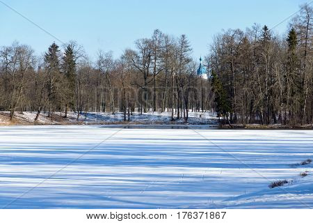 spring landscape of the frozen river with a thawed patch and wood with church on a background