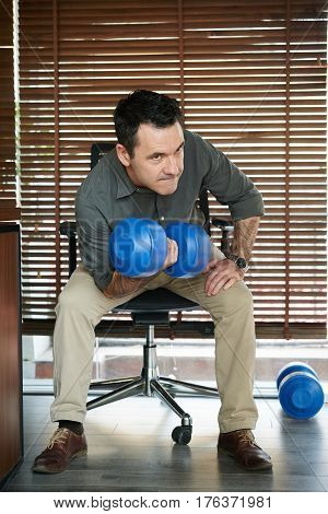 Mature man lifting dumbbells during break at office
