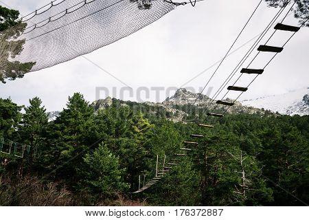 Zip line in woodland against snow capped mountain range. Navacerrada Madrid Spain