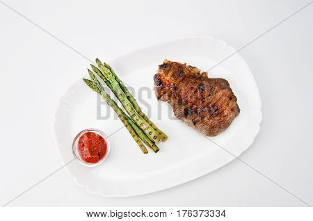 Grilled beef steak with asparagus and red sauce on a white plate, over white background