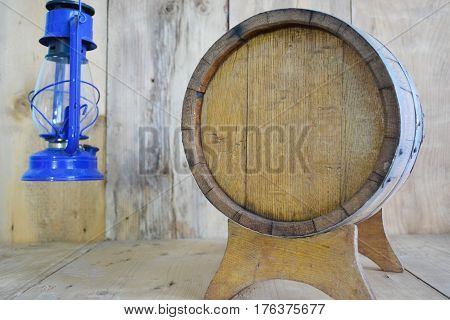 background of barrel and worn old table of wood and kerosene lamp