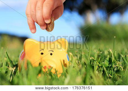 Baby hand and piggybank over nature background.