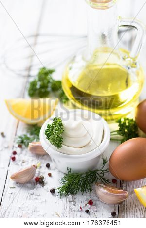 Mayonnaise sauce and ingredients on white wooden table.