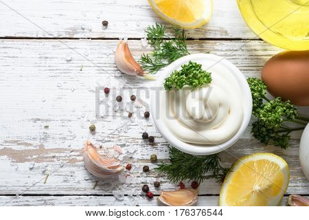 Mayonnaise sauce and ingredients on white wooden table. Top view