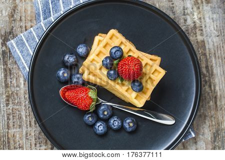 Morning Waffles with berries on a dark plate
