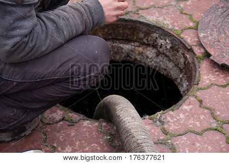 man pumping sewage from the drain hole.