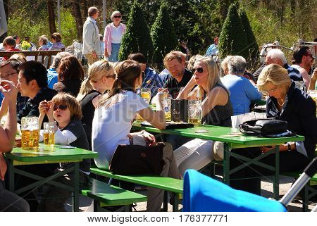 Munich,Germany-April 2,2011:People sit in a beergarden in a park enjoying the sunny weather