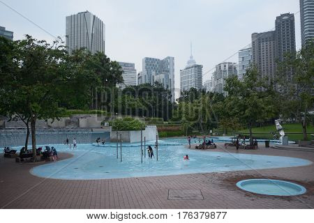Kuala Lumpur Malaysia - November 5 2014: People relaxing in the KLCC Park in Kuala Lumpur Malaysia. This city park was designed by Brazilian architect Roberto Burle Marx.
