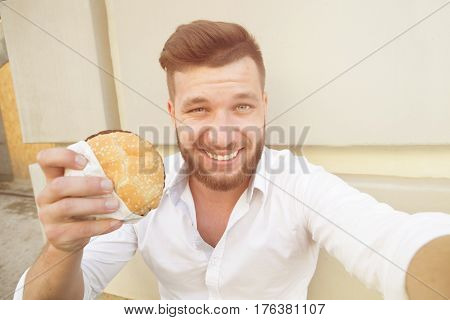 Hungry businessman making selfies with hamburger during his lunch time. Smiling short-haired man resting outdoors. Toned image.