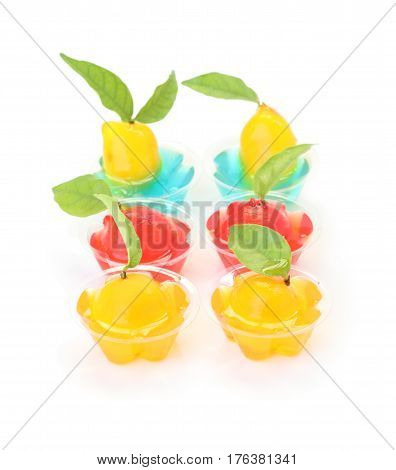 Deletable imitation fruits in jelly cup on white floor.
