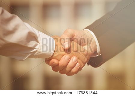 Business handshake, the deal is finalized between two enterprises. Man in black suit and woman in white one have signed the agreement. Toned image.