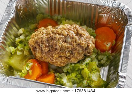Healthy lunch foil container closeup. Diet nutrition in foil boxes. Steamed minced meat cutlet with vegetables