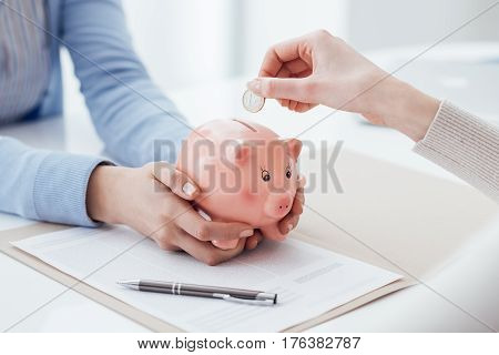 Financial advisor holding a piggy bank and customer inserting a coin: investments savings plan and retirement fund concept