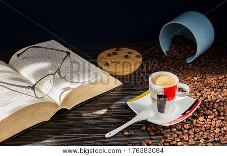 A cup of morning coffee. A bank and a lid with an inscription of coffee. The coffee is sprinkled on the table.An open thick book, on the book glasses.