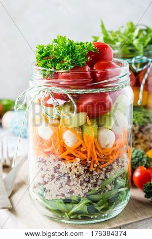 Glass jar with quinoa and vegetables salad. Healthy food, diet, detox, clean eating and vegetarian concept.