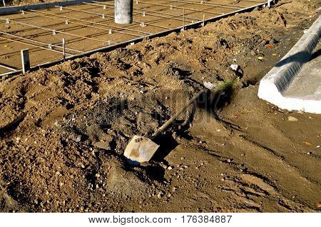 A shovel lies in the sand at a sidewalk and curb construction project with the rebar for added strength lies in place