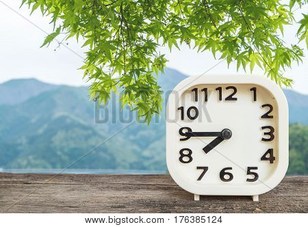 Closeup white clock for decorate show show a quarter to eight o'clock or 7:45 a.m. on blurred green leaves and mountain view background