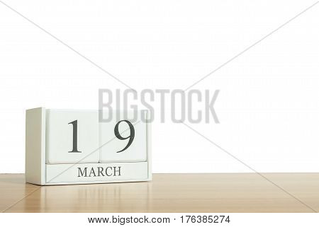 Closeup surface white wooden calendar with black 19 march word on blurred brown wood desk isolated on white background with copy space selective focus at the calendar