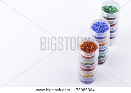 Storage system for glass seed beads. Colored glass seed beads in tubes for jewelry making and beading process on white background. Hobby handmade fine arts. Selective focus.